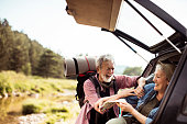 Close up of senior couple grabbing their hiking gear from the car and going hiking