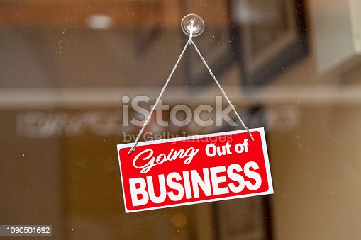 Red sign hanging at the glass door of a shop saying: