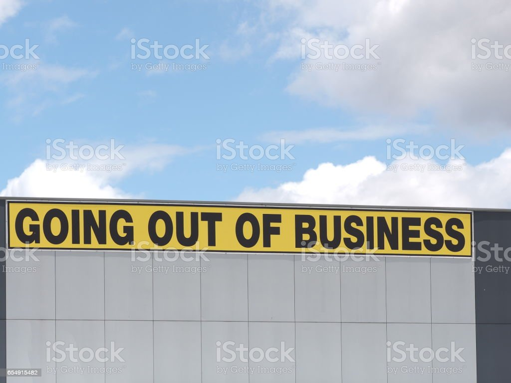 Going out of business writing in black on yellow letters on a white cladded industrial building, Melbourne 2016 stock photo