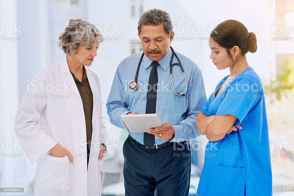 Shot of three healthcare professionals looking over medical records...