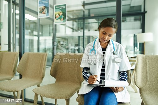 Shot of a young doctor sitting in the waiting room of a clinic