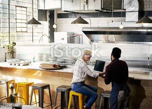 Cropped shot of a mature woman talking to a staff member while going over her coffee shop's finance