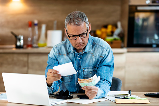 Confused frustrated mature man holding mail letter and money in the kitchen, reading shocking unexpected news nonsense in paper document, mad about high bill tax invoice, debt notification, bad financial report, money problem.