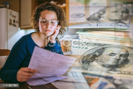 Young woman is looking at bills, feeling worried. Tax paying, bills, utilities concepts. Composite image.