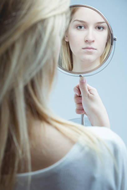 Going through difficult time of her life Close-up of a young, upset woman looking in the mirror she is holding in her hand low self esteem stock pictures, royalty-free photos & images