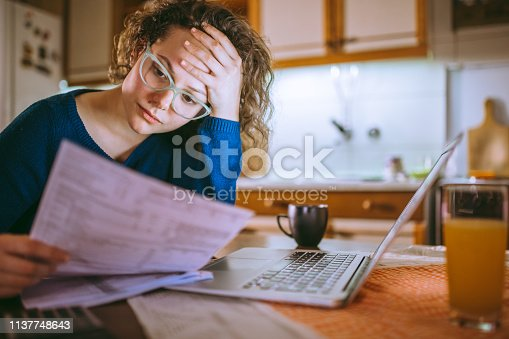 Young female reading documents, using laptop in the kitchen at home