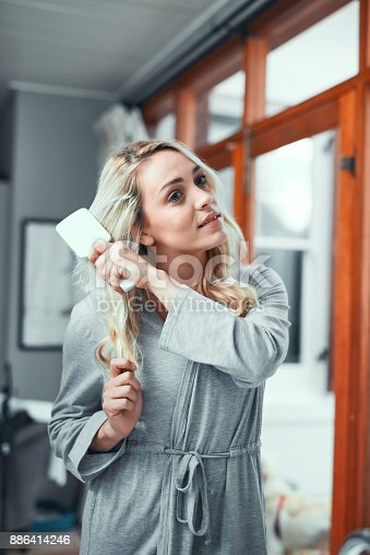 886414246istockphoto Going through her haircare routine 886414246