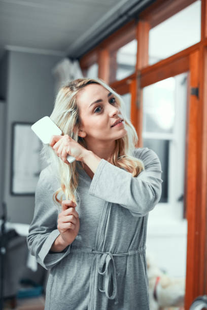 Going through her haircare routine Shot of a young woman brushing her hair at home combing stock pictures, royalty-free photos & images