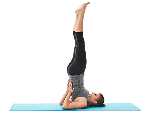 Going through her yoga regime An attractive young woman stretching her back out isolated on white shoulder stand stock pictures, royalty-free photos & images