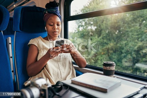 Cropped shot of an attractive young woman sitting and wearing earphones while listening to music from her cellphone