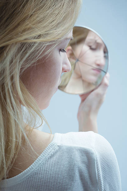 Going through painful moments in her life Close-up of a young woman looking into a broken mirror with grim face low self esteem stock pictures, royalty-free photos & images