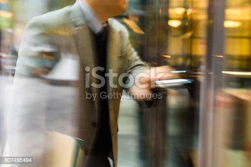 Businessperson walking through the revolving door in motion blur