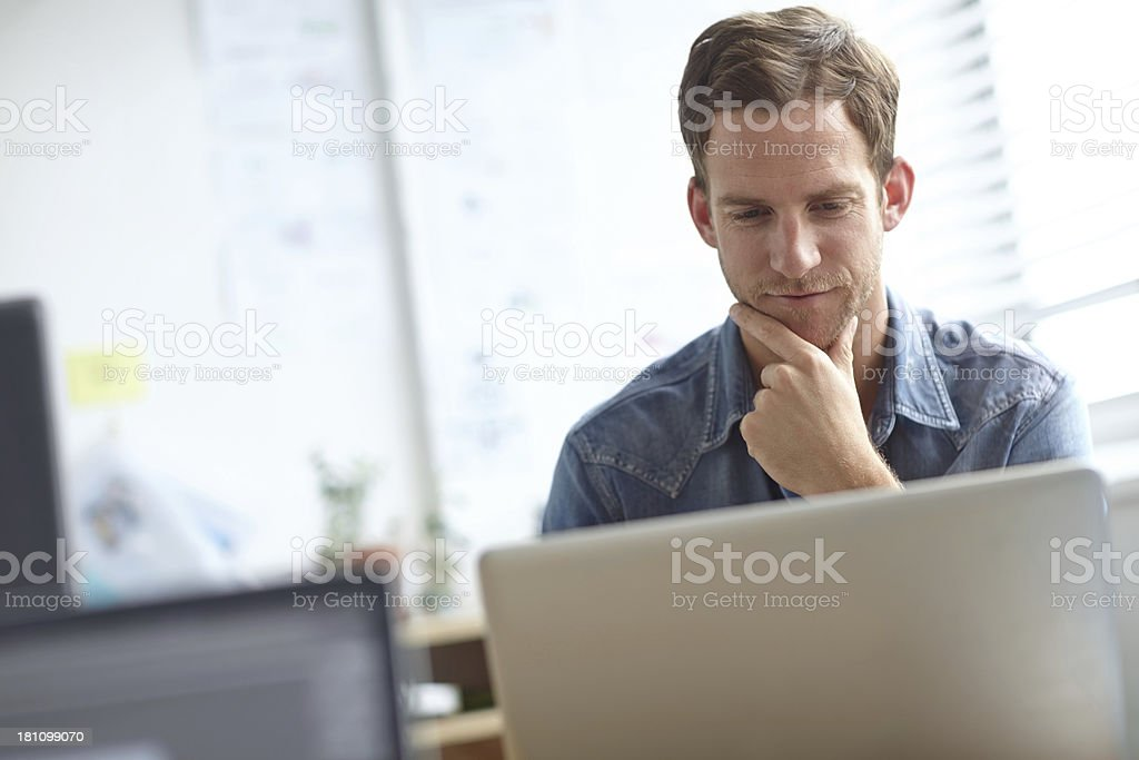 Going through the project thoroughly... A handsome young man working on his laptop in the office 20-24 Years Stock Photo