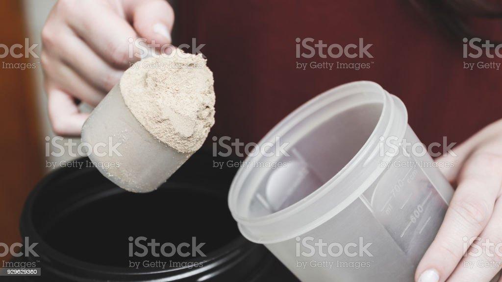 Vai para derramar pó de proteína de caseína no copo. - foto de acervo