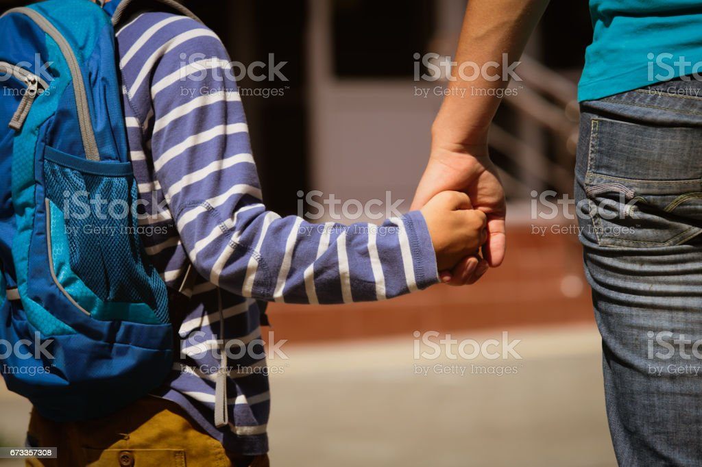 going to school- mother holding hand of son stock photo