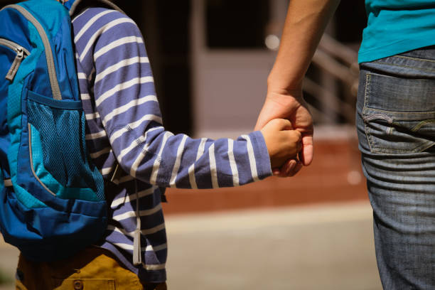 going to school- mother holding hand of son - vakta bildbanksfoton och bilder
