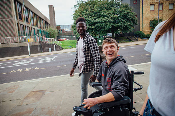 Going to Town Three friends walking down the street together. One is quadriplegic and is in a wheelchair. Both guys are laughing and looking at the girl, who is only partially in shot. paraplegic stock pictures, royalty-free photos & images