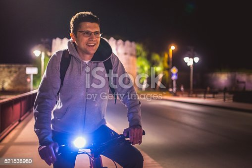 Man riding a bicycle at night the city