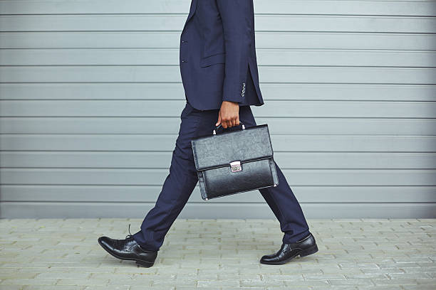 Going to work Legs of businessman in suit walking to work in the morning briefcase stock pictures, royalty-free photos & images