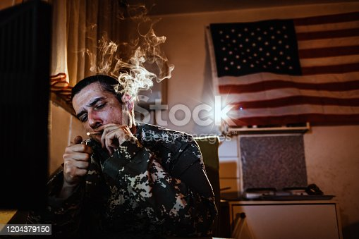 Young soldier man smokes at home while sitting in wheelchair. Blows the smoke at night with American flag in background.