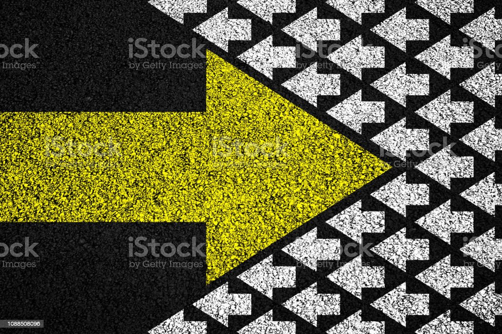 Going your own way on asphalt background Going your own way concept. Big yellow arrow in reverse direction in relation to many white arrows, on asphalt background. Abstract Stock Photo