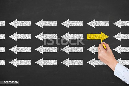 579158952 istock photo Going Your Own Way with Arrows Symbol on Blackboard Background 1206704389