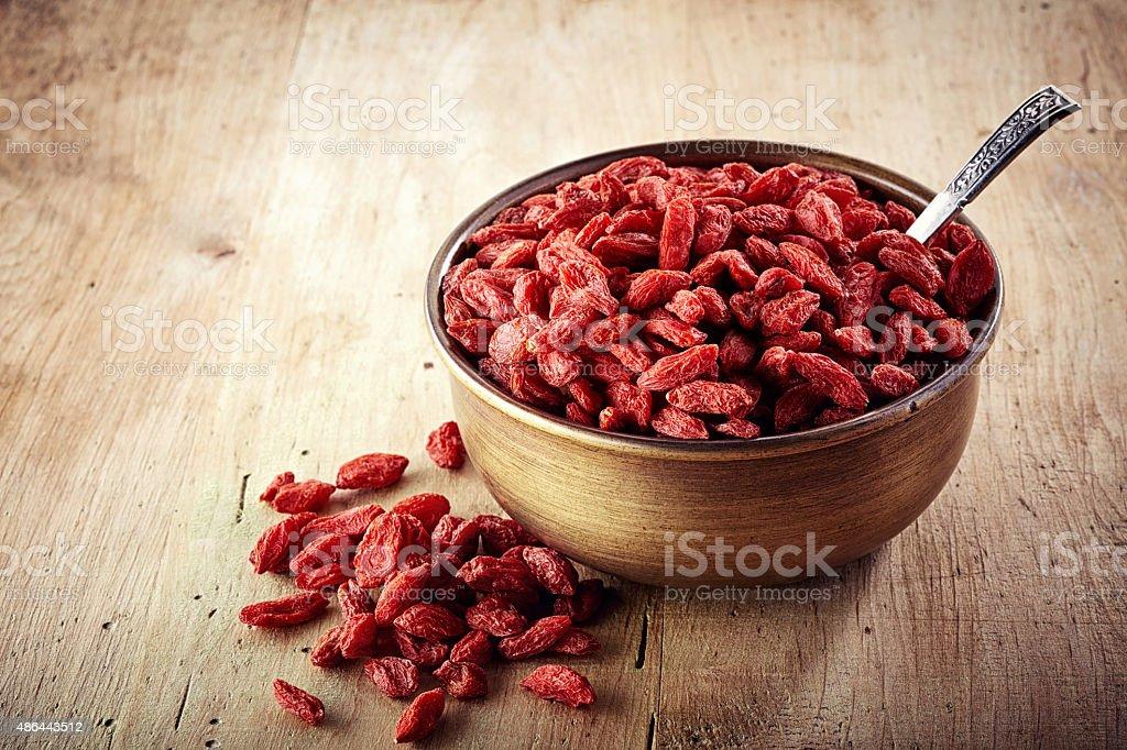 Bowl of goji berries on wooden background