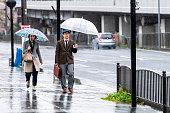 雨の日の五条通りと歩道で傘を持って歩く人々