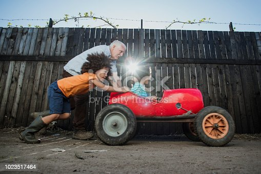 Little boy is being pushed in a homemade go kart by his brother and grandfather.