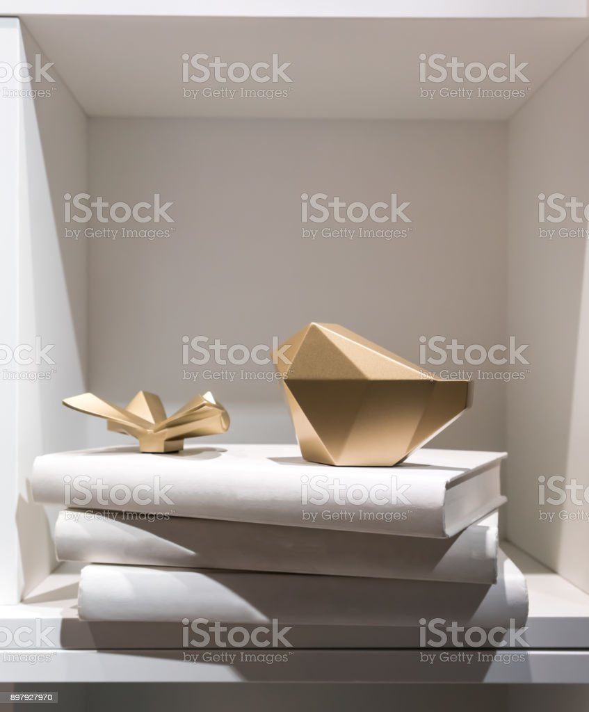 Gold abstract paperweight placing on a stack of white cover books on wooden shelf. stock photo