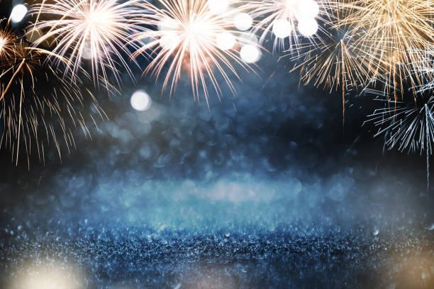 fuegos artificiales de oro y azul y bokeh en la víspera de año nuevo y copiar espacio. vacaciones de fondo abstractas. - año nuevo fotografías e imágenes de stock
