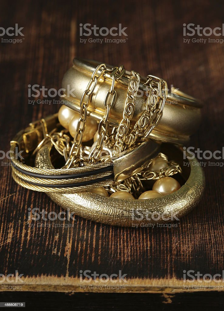 gold and pearl jewelry on vintage wooden background royalty-free stock photo