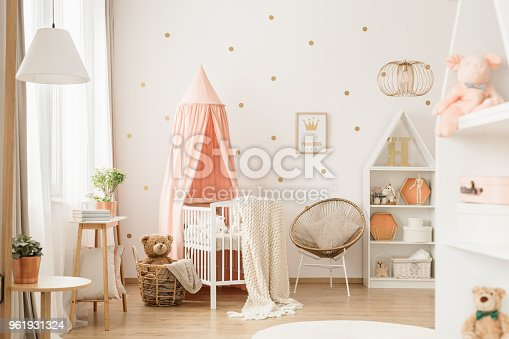 Canopied cradle between gold armchair and basket with teddy bear in pink baby's bedroom interior