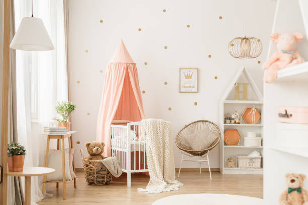 Gold and pink baby's bedroom Canopied cradle between gold armchair and basket with teddy bear in pink baby's bedroom interior bedroom stock pictures, royalty-free photos & images