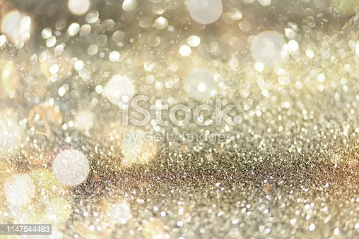 881350776 istock photo Gold and silver abstract bokeh lights. Shiny glitter background with copy space. New year and Christmas concept. Sparkling greeting card 1147544463