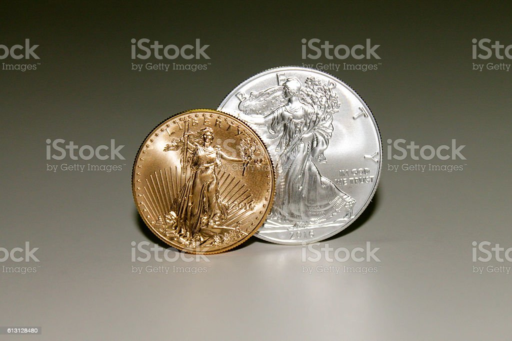 Gold and Silver Coin Standing Side by Side stock photo