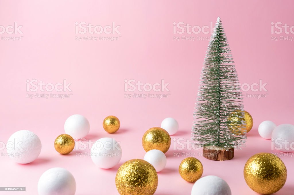 Gold and white glitter ball decoration with small Christmas tree on...