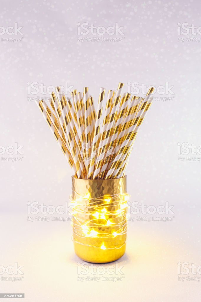 Gold and white paper straws in the golden glass. Christmas concept....