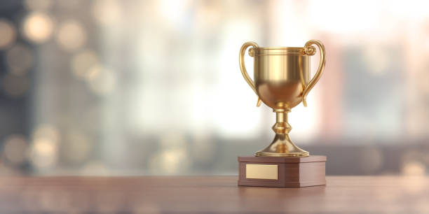 gold award cup against defocused background - trophy award stock photos and pictures