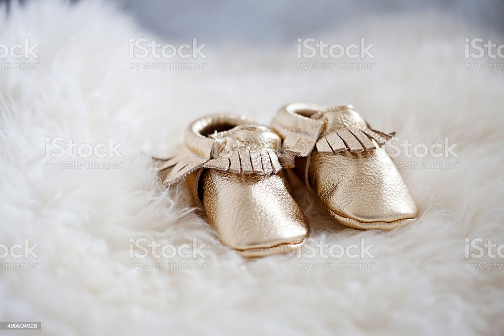 Gold baby moccasins on a fur rug stock photo