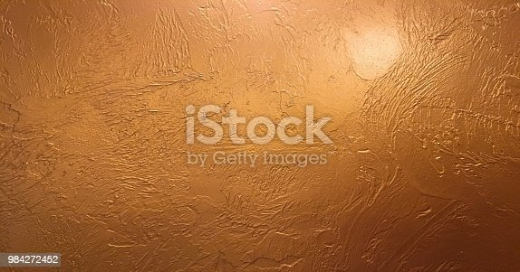 istock Gold background or texture and gradients shadow. Shiny yellow leaf gold foil texture background. Gold background paper, texture is old vintage distressed solid glitter gold color with rough peeling grunge paint on edges. 984272452