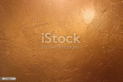 istock Gold background or texture and gradients shadow. Shiny yellow leaf gold foil texture background. Gold background paper, texture is old vintage distressed solid glitter gold color with rough peeling grunge paint on edges. 984272586