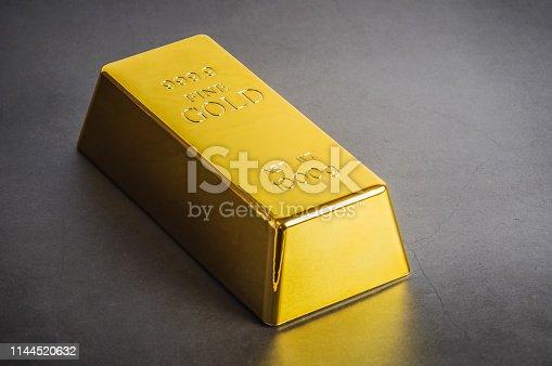 istock Gold bar ingot bullion on a gray background. Located diagonally. 1144520632