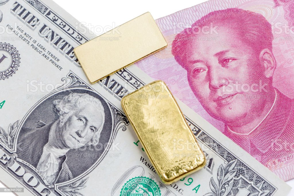 Gold bar over the US dollar bill and Chinese yuan banknote on white background, economy finance concept. stock photo