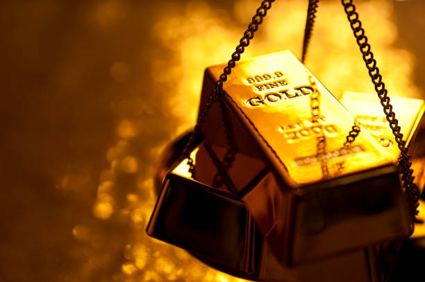 Gold bars on weight scale stock photo