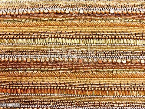 istock gold beaded background 517582586