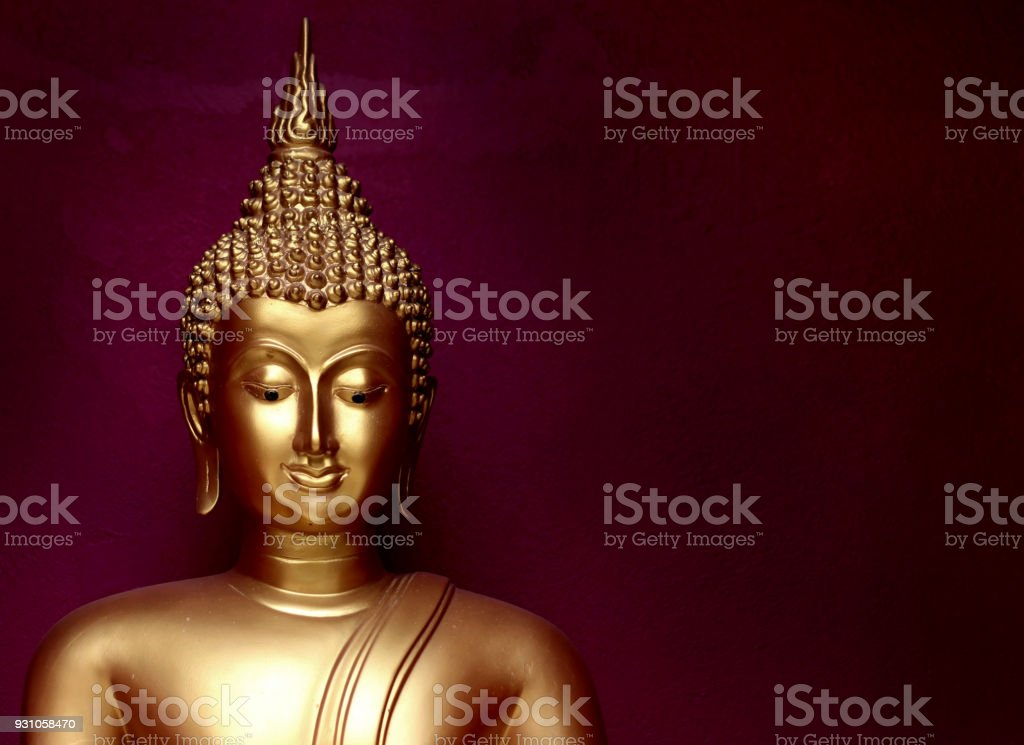 gold bhuddha statue close up smile face on vintage dark red background low key style stock photo