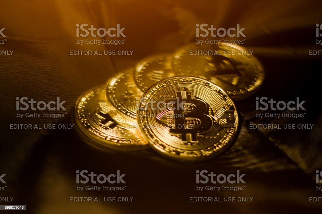 Gold Bitcoin coins on black silk background stock photo