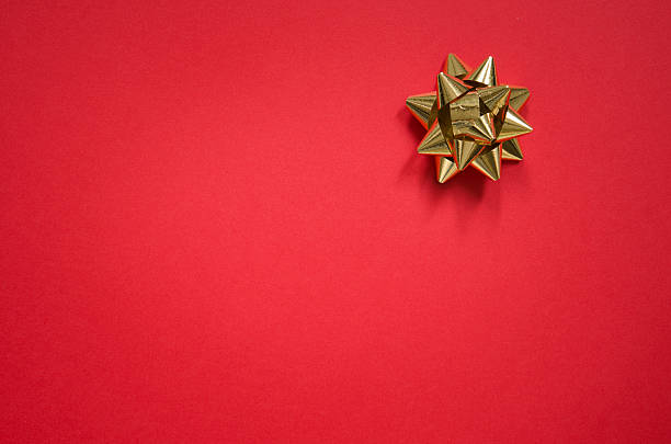 gold bow on christmas red background - wrapping paper stock photos and pictures