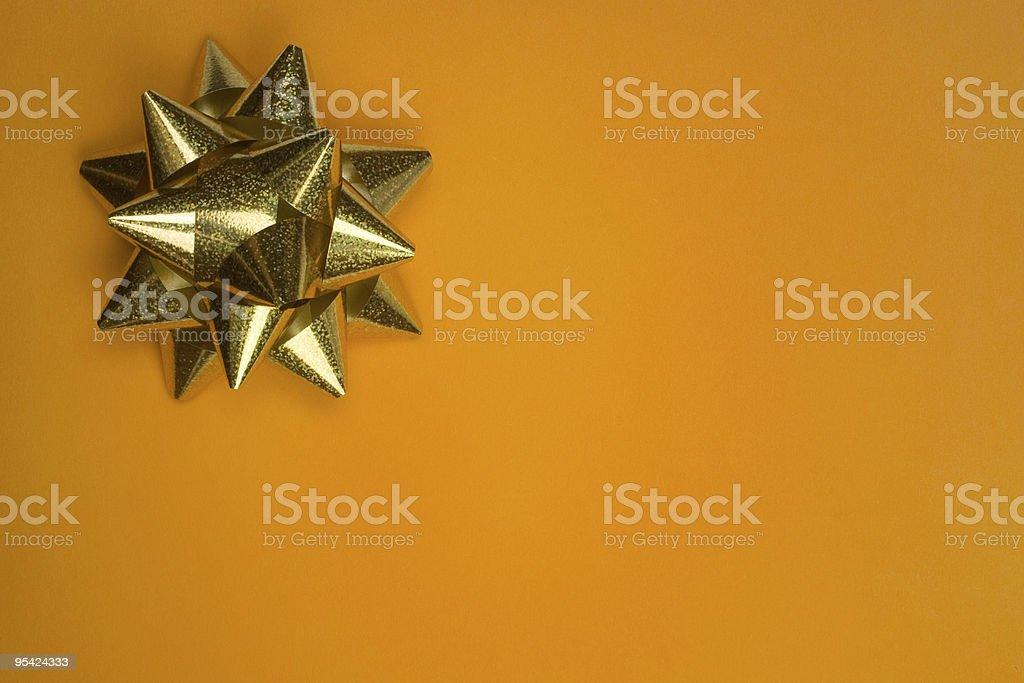 Goldene Schleife auf orange Karte Lizenzfreies stock-foto